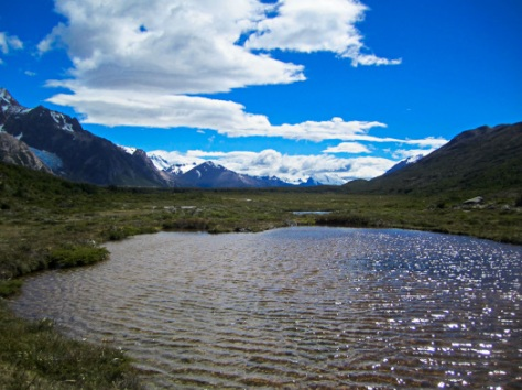 Crossing a valley in Parque los Glaciares before reaching the mountains. Glaciers shine in the distance.